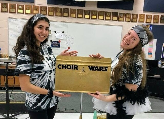 Winning Victory: East High School won the golden music stand for the second time in a row, Lisa Marie Museracia (left) and Renee Sonnet (right) pose with the musical stand that they won and smile bright. Photo taken by John Methias .