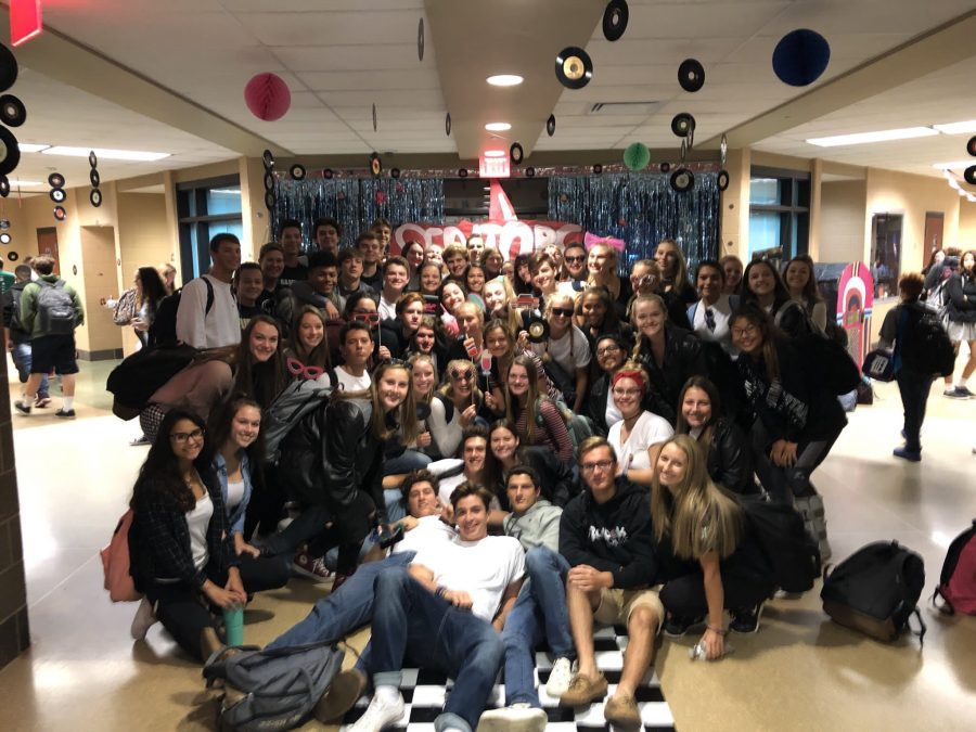 Seniors take a photo together in their hallway.